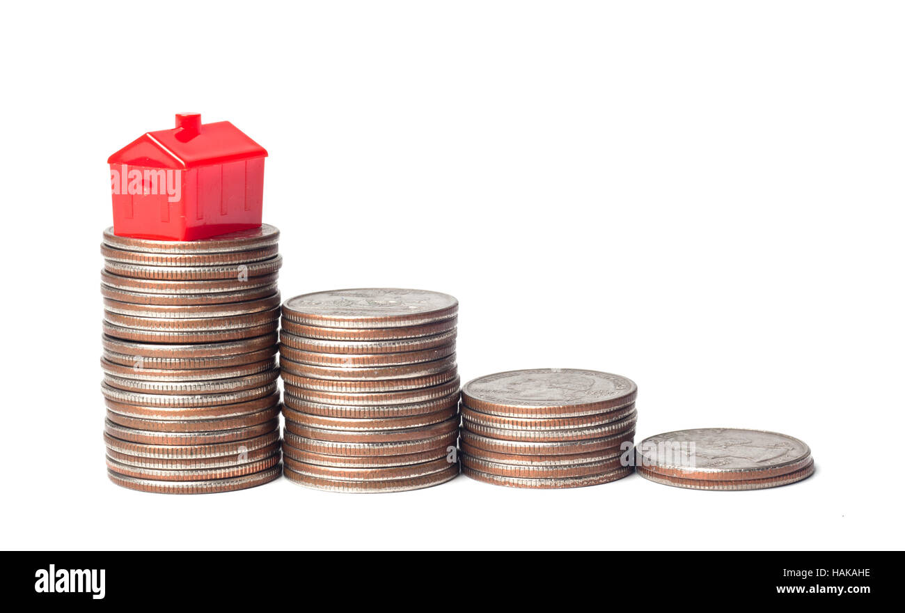 Toys house and pile of coins representing financial goal of home ownership - Stock Image