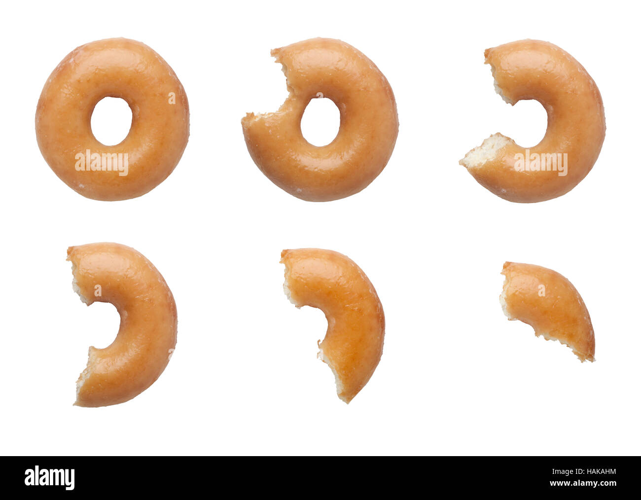 Sequence of bites taken off a donut isolated on white background - Stock Image