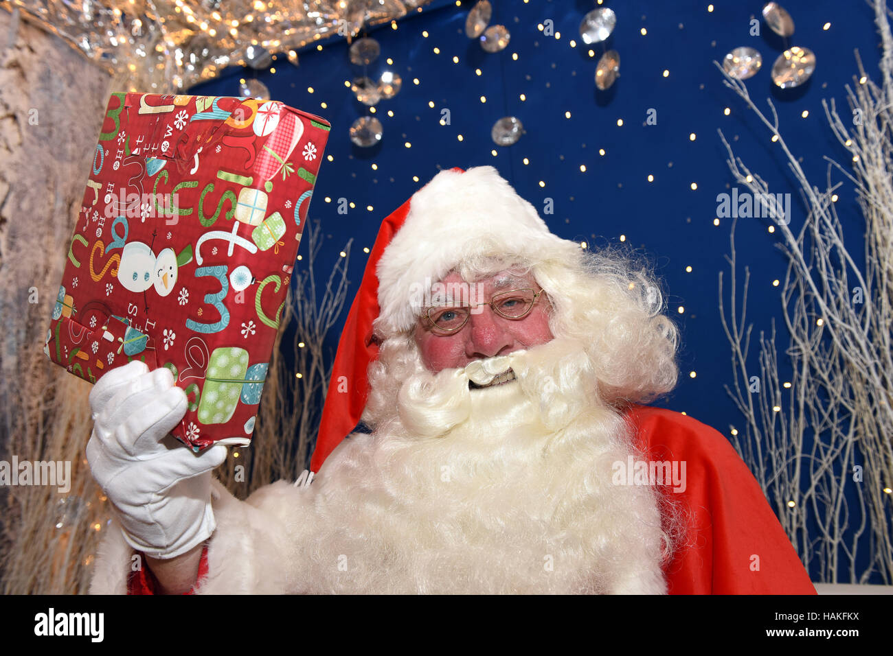 Santa Claus or Father Christmas handing out gifts in his grotto - Stock Image