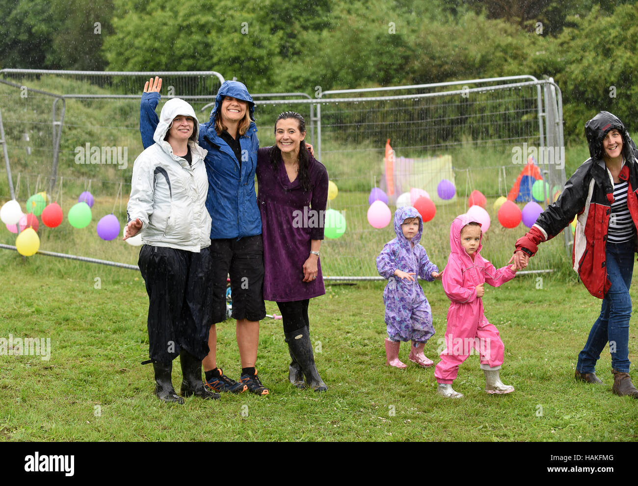 Smiling in the rain! Women and children having fun despite wet weather at an English summer fete Uk - Stock Image