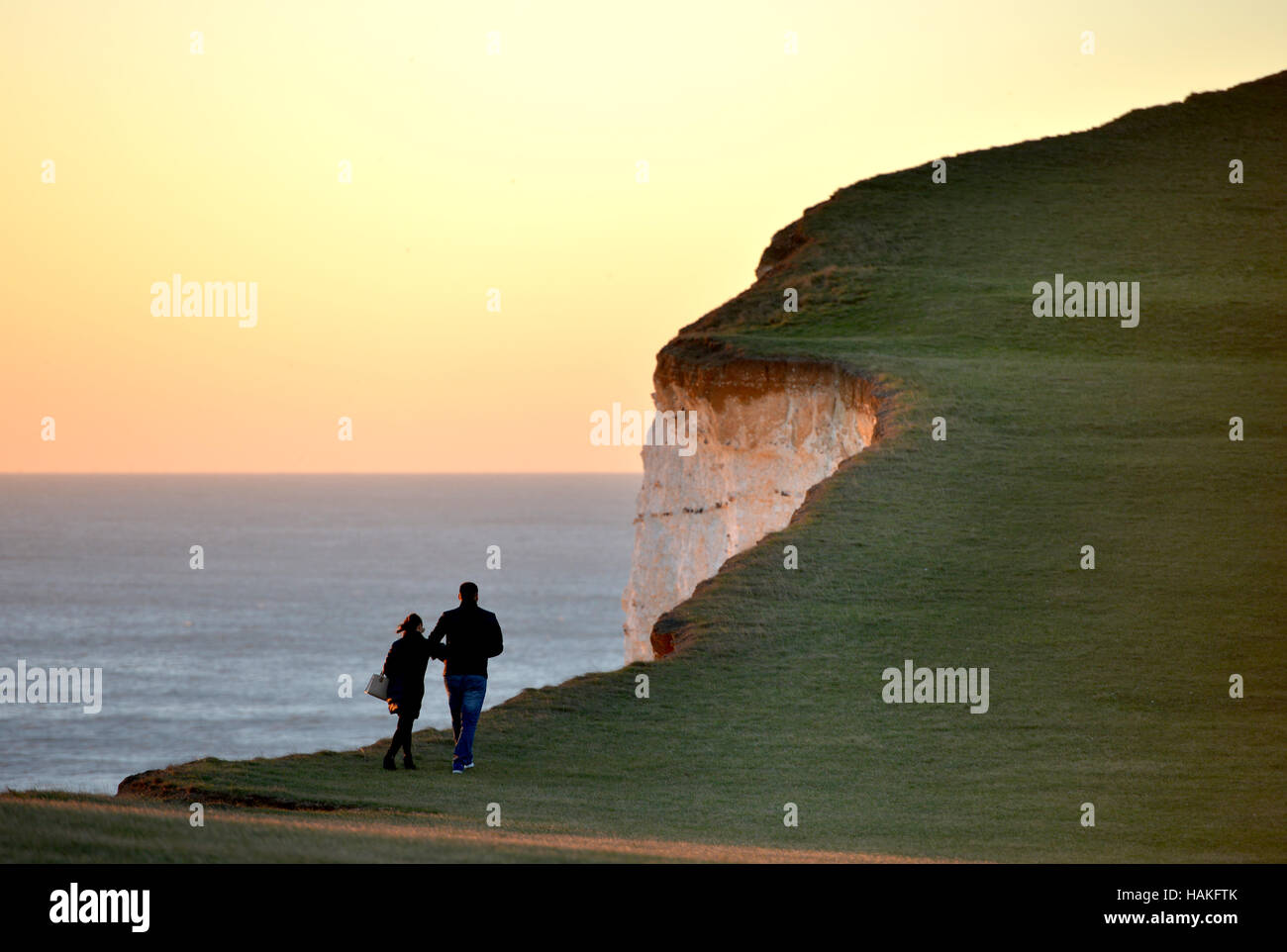 Couple walking near to the cliff edge at Beachy Head, famous suicide spot in East Sussex. - Stock Image