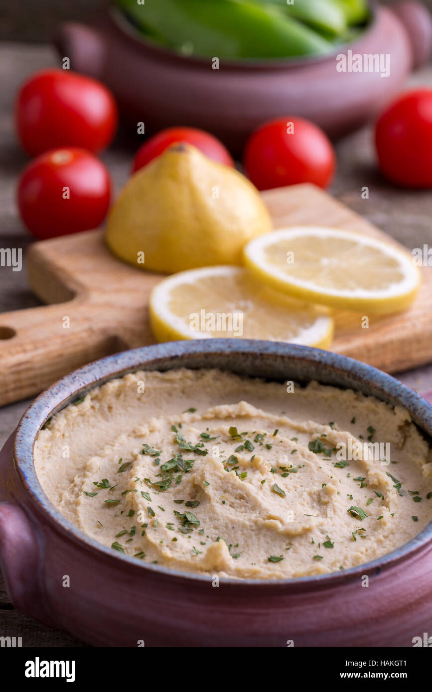 Humus in homemade bowl with vegetable around. - Stock Image