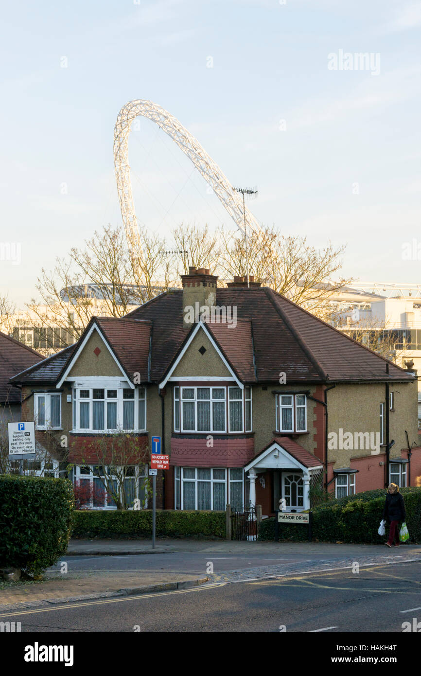 The arch of Wembley Stadium seen over the roofs of suburban houses Wembley, London. - Stock Image