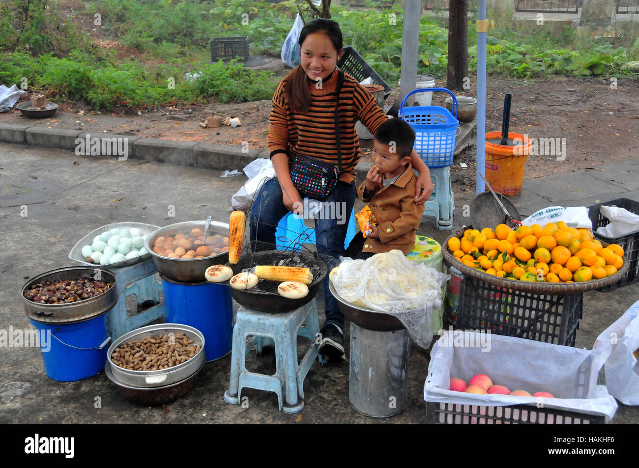 Vendors, such as this mother and son, often sale food along the roadway in some areas of China. Stock Photo