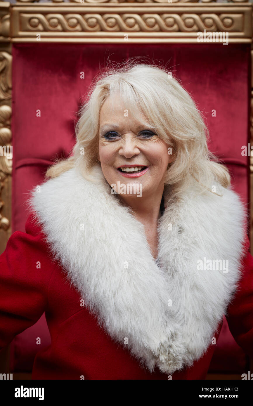 Born in Nottingham Sherrie Hewson posed portraits wearing a red santa style coat - Stock Image