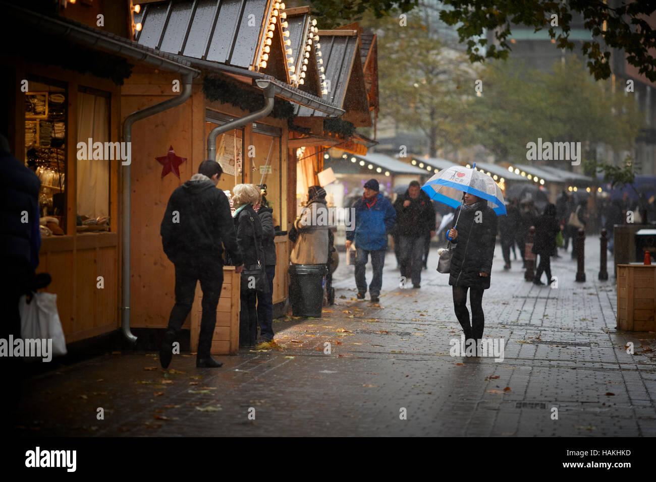 Manchester christmas markets rain  I love MCR umbrella up used street wooden huts wet dull winter scene Market bazaar - Stock Image