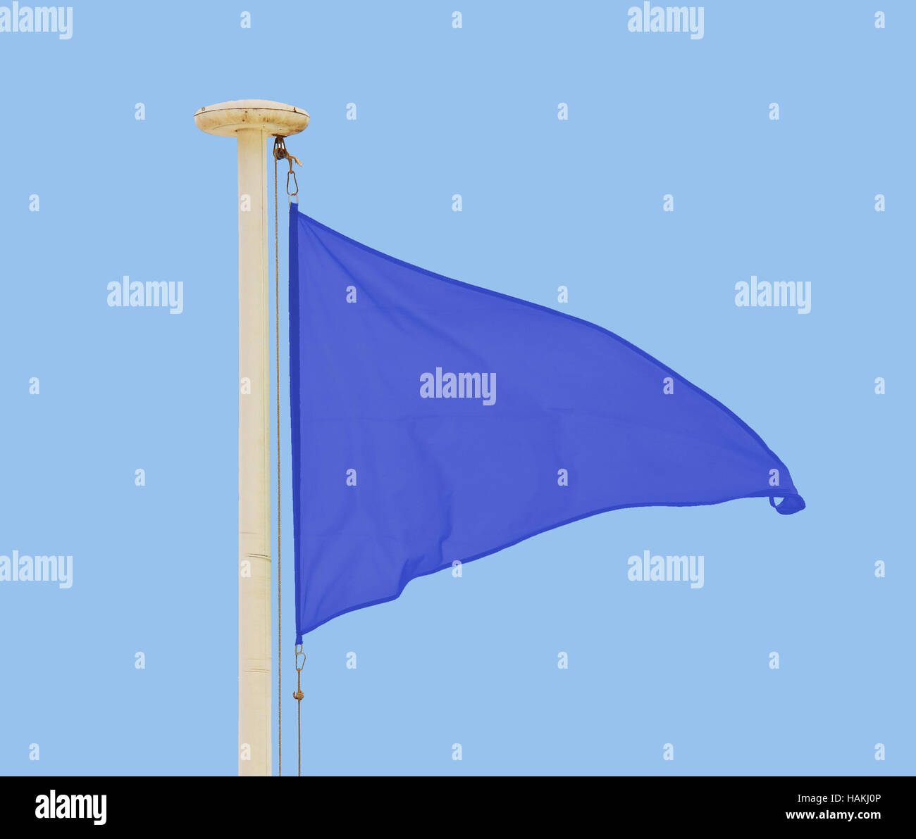 Blue pennant flying in a brisk breeze against a pale blue sky - Stock Image
