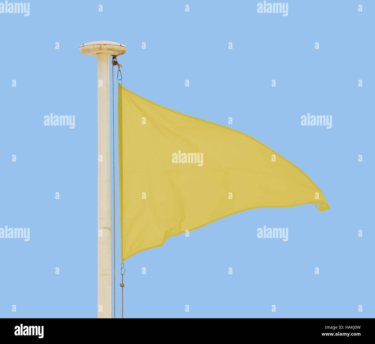 Yellow pennant flying in a brisk breeze against a pale blue sky - Stock Image