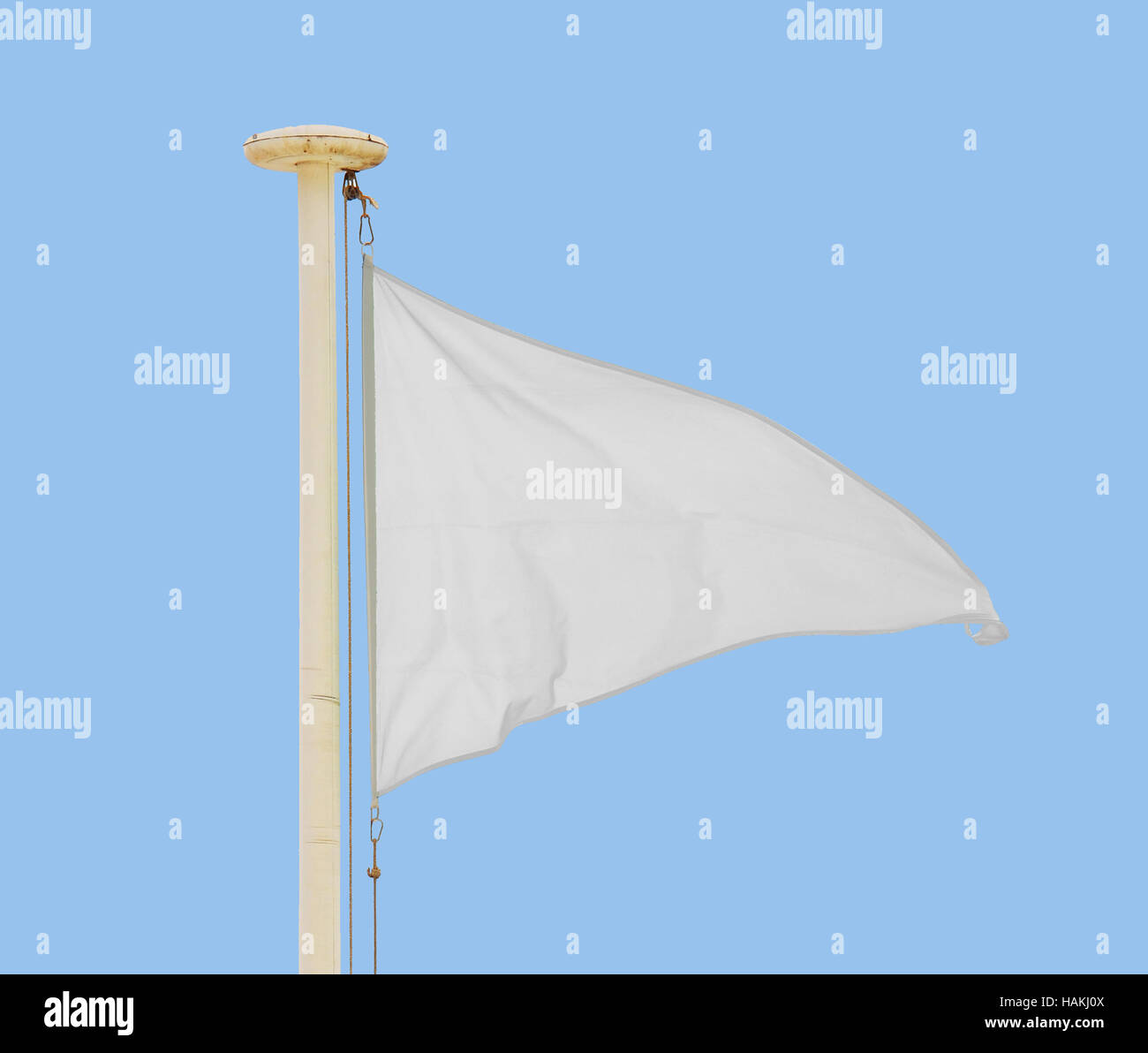 White pennant flying in a brisk breeze against a pale blue sky. - Stock Image