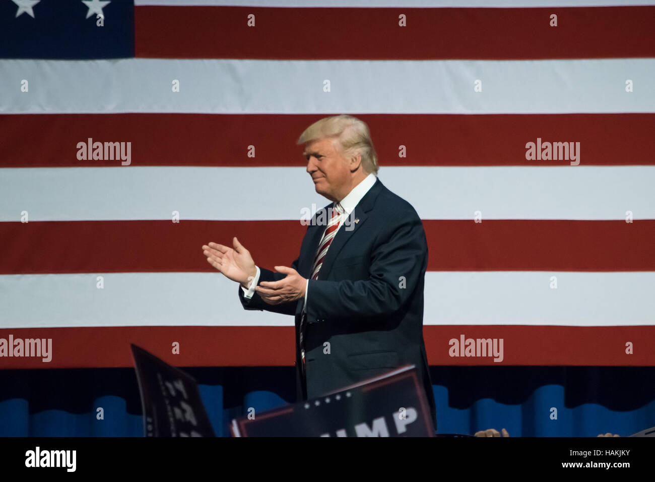 Republican Presidential Nominee Donald Trump walking on stage applauding the crowd near the American Flag. - Stock Image