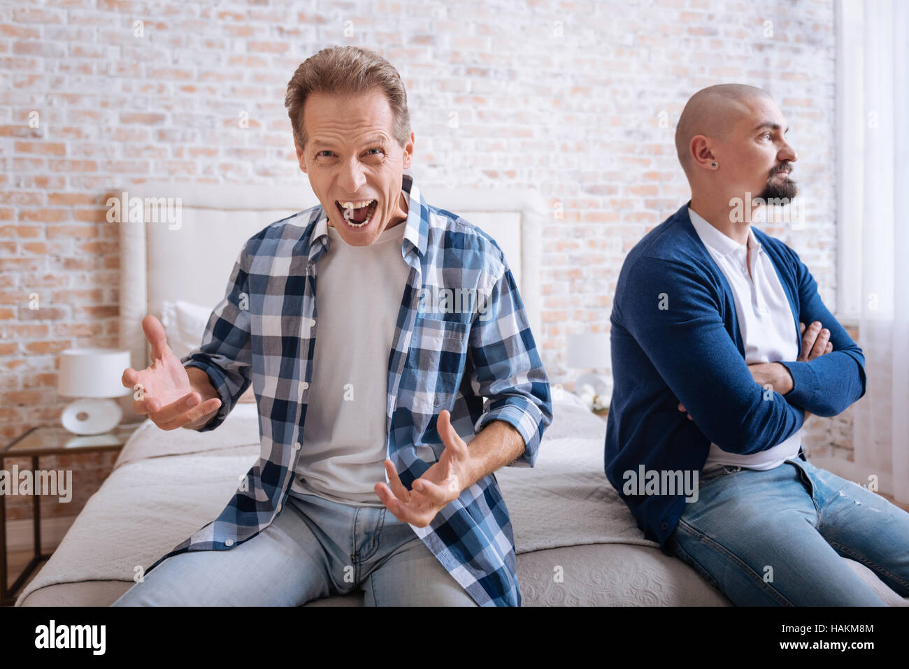 Inflamed man screaming loudly at home - Stock Image