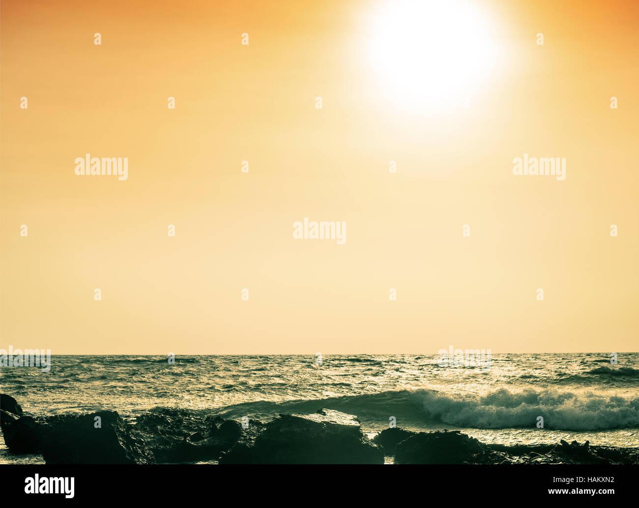 stone shore at sunset - Stock Image