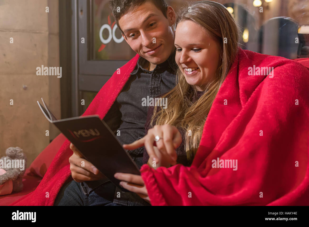 Happy couple with menu at restaurant terrace. Love, dating, people, holidays concept - Stock Image