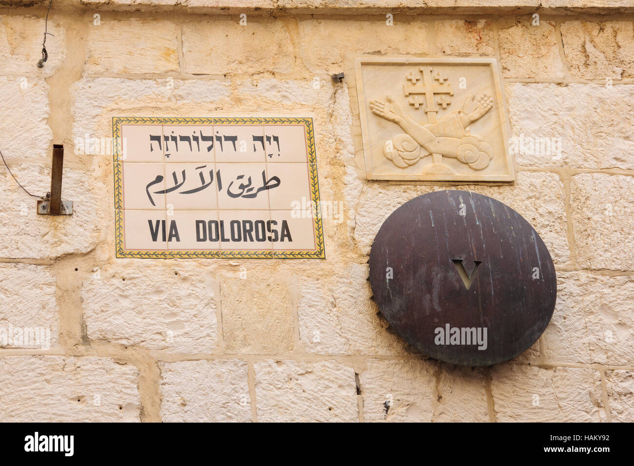 A mark of station 5 of the Via Dolorosa, and a street sign, in the old city of Jerusalem, Israel Stock Photo