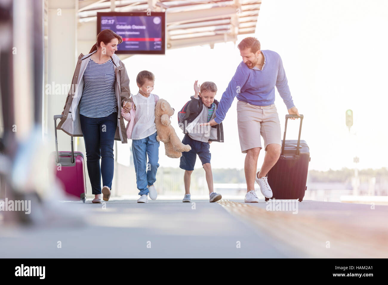 Family walking pulling suitcases at train station - Stock Image