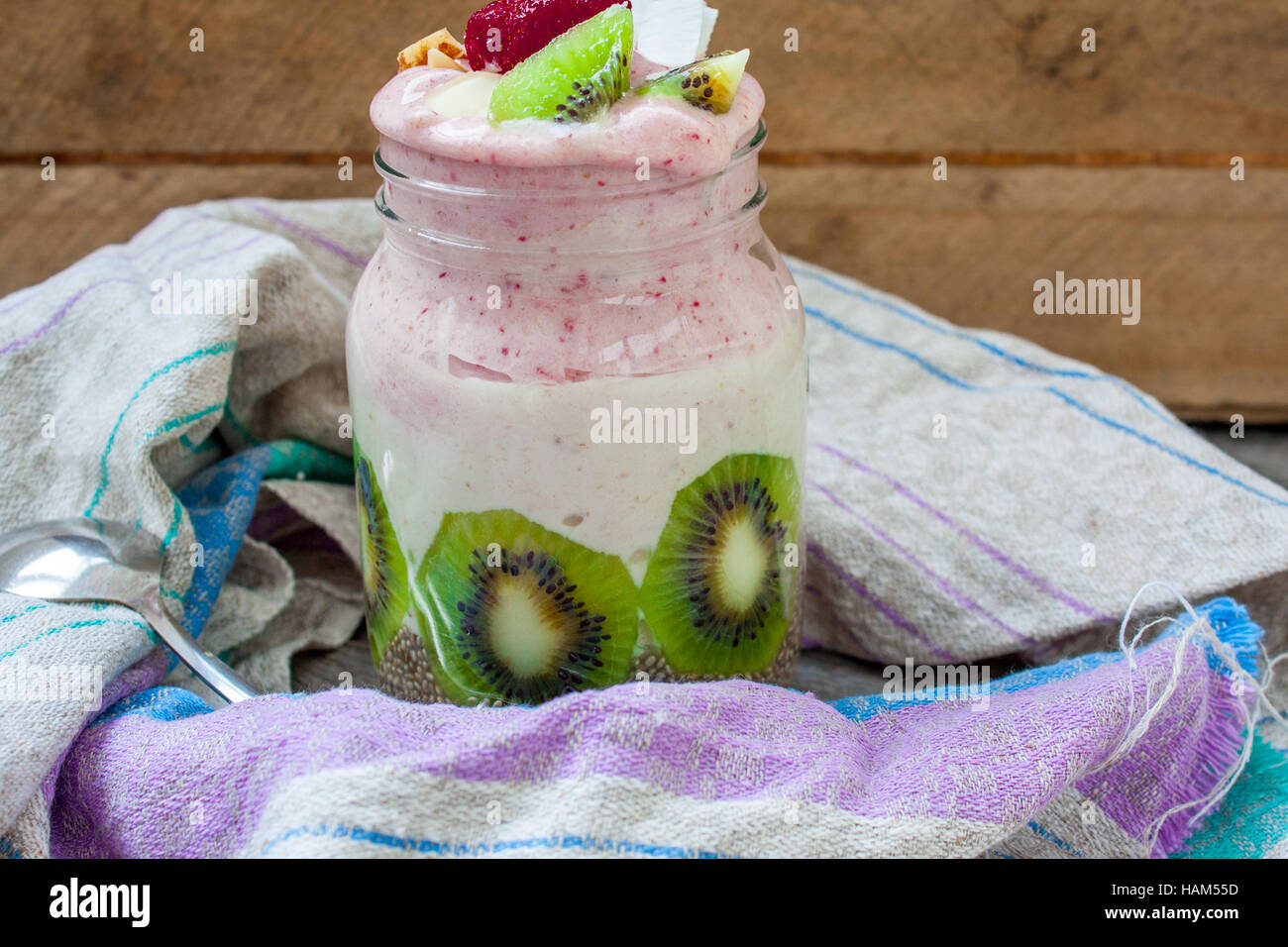 Banana-strawberry smoothie with kiwi, chia, nuts and coconut in a jar. Perfect for the detox diet or just a healthy - Stock Image