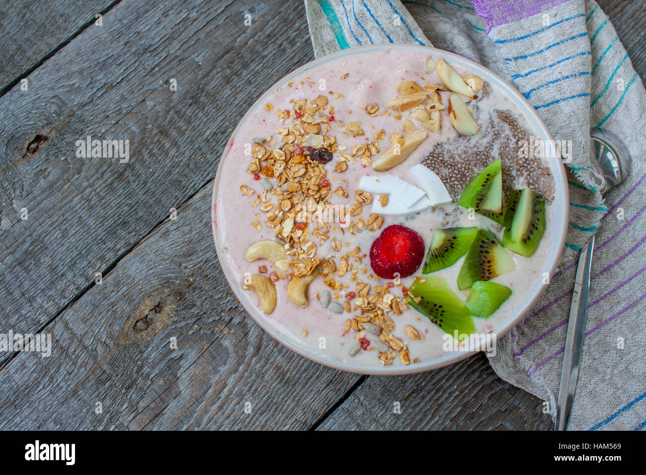 Banana-strawberry smoothie with kiwi, chia, muesli with nuts and coconut in a bowl. Perfect for the detox diet or - Stock Image