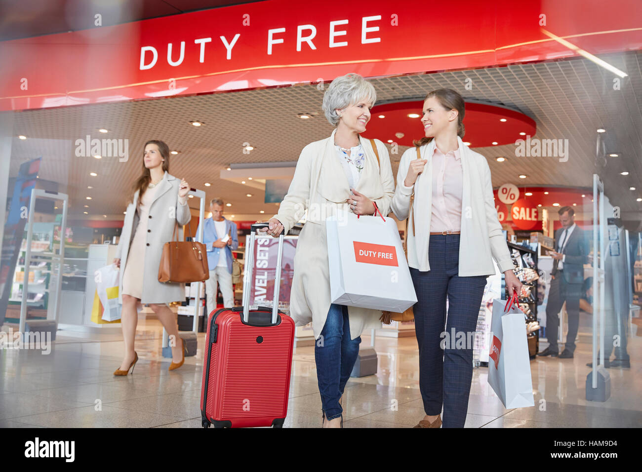 Women leaving airport duty free shop with shopping bags and suitcase - Stock Image