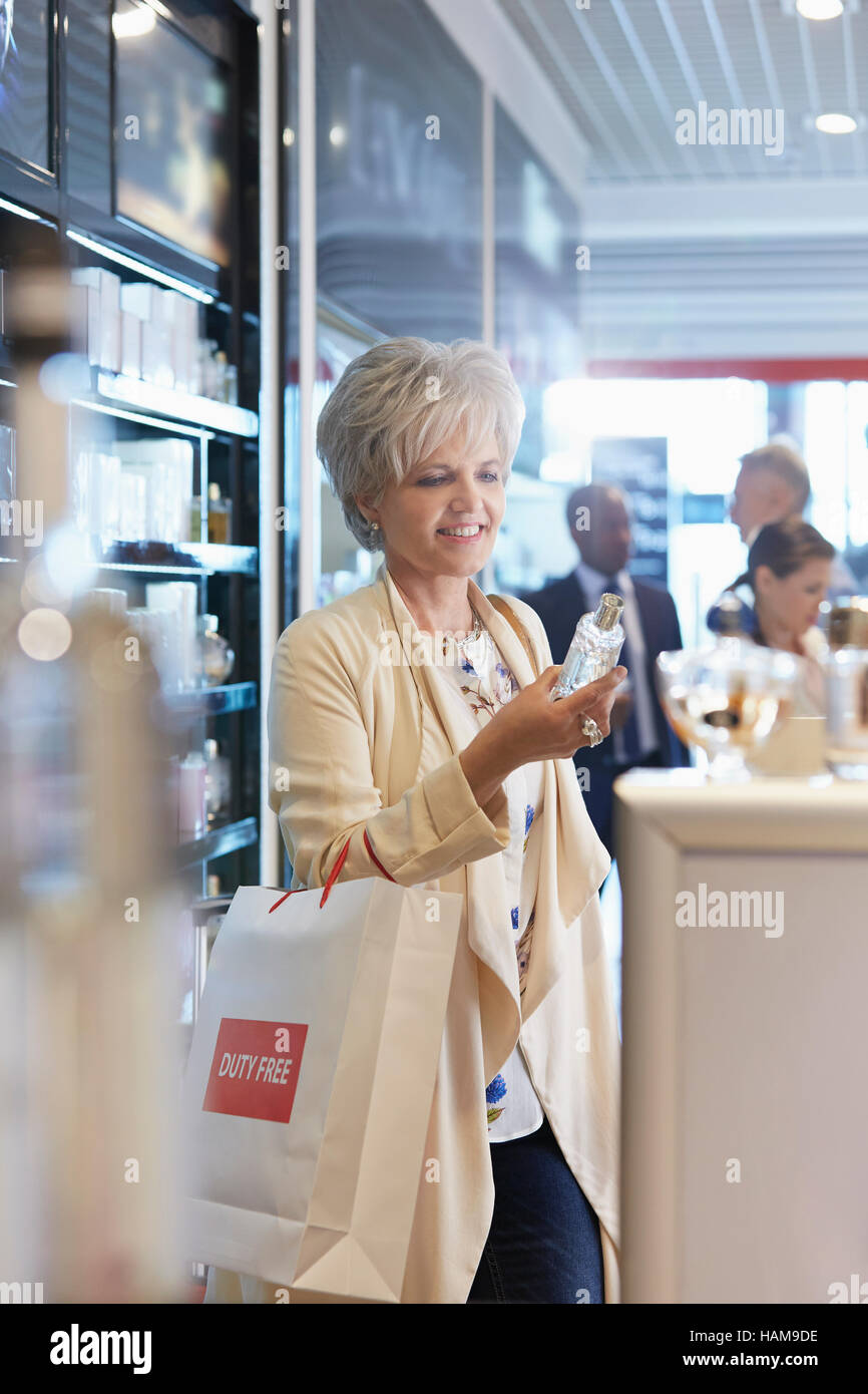 Woman shopping for perfume in airport duty free shop - Stock Image