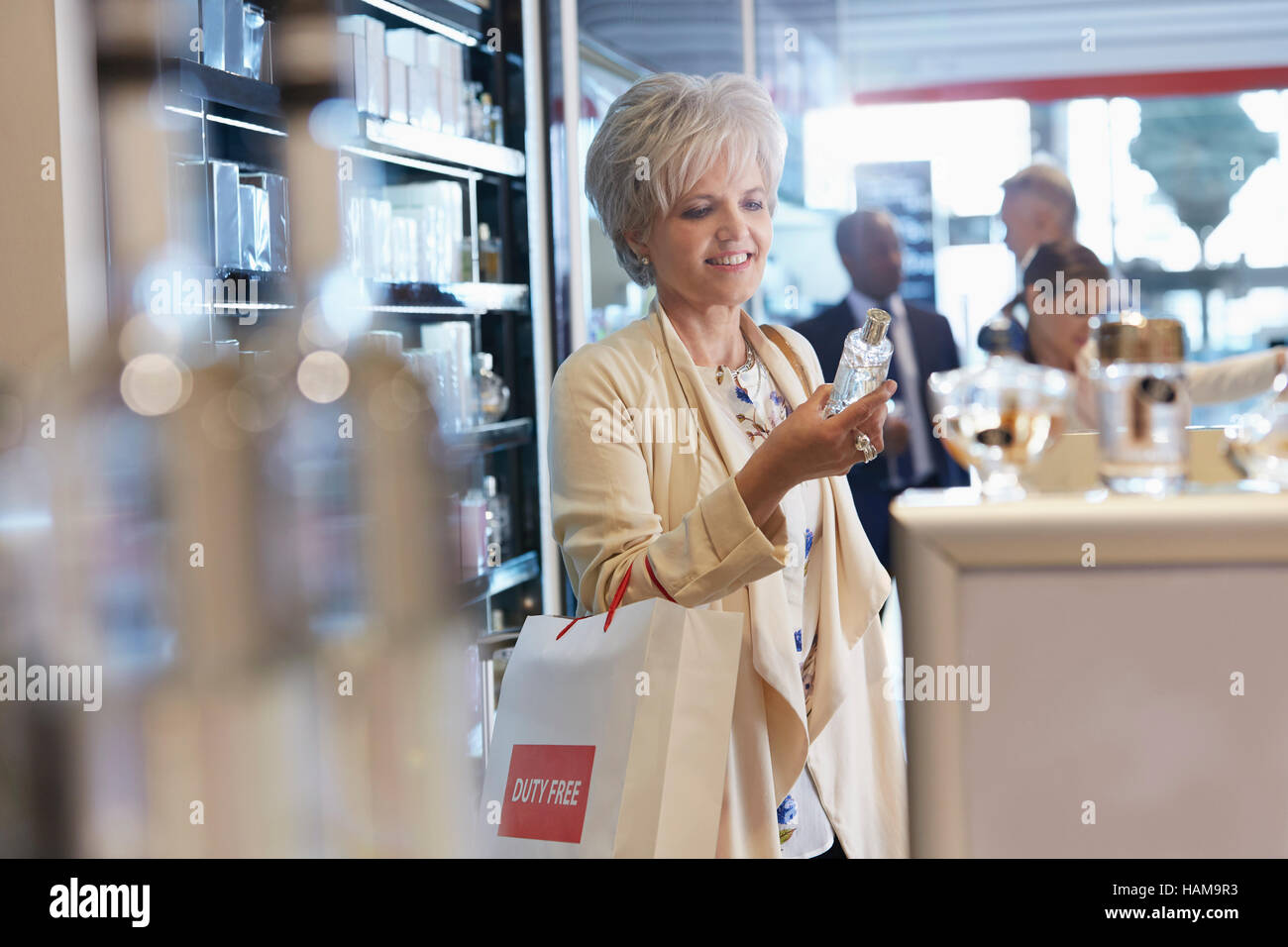 Smiling woman shopping for perfume in duty free shop - Stock Image