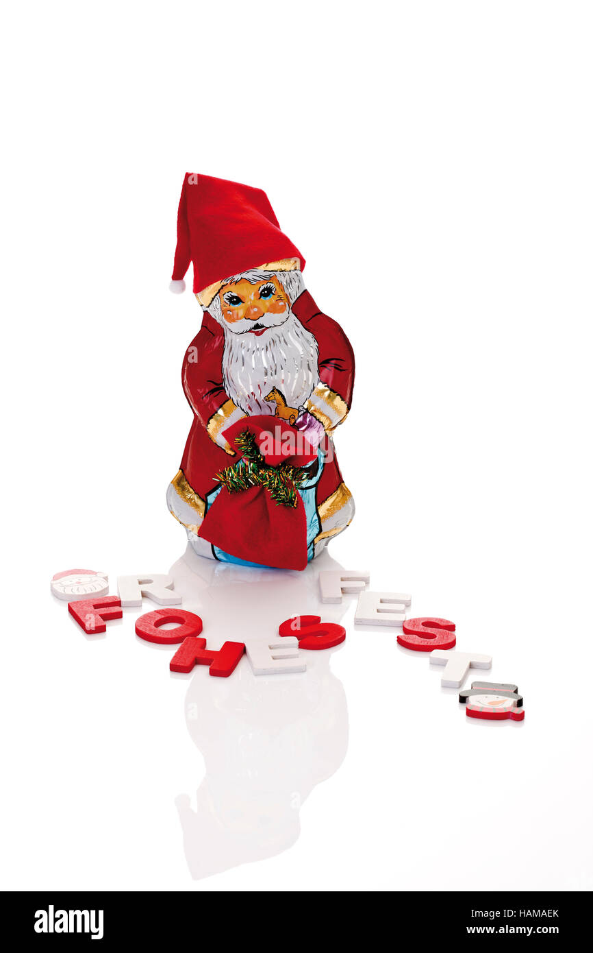 Chocolate Santa Claus and the letters, Frohes Fest, German for Merry Christmas - Stock Image