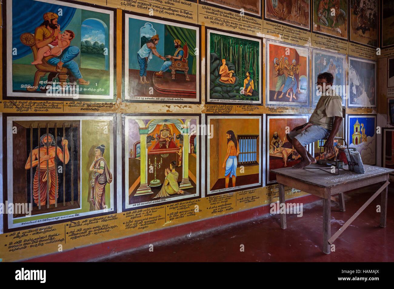 Singhalese man restoring murals, scenes from life of Buddha, Weherahena Temple, Matara, Southern Province, Sri Lanka - Stock Image