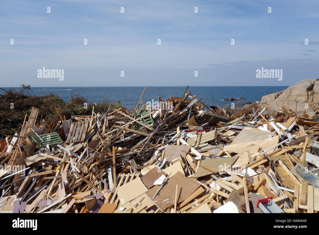 Dumping ground for discarded wood on the coast of Öckerö island, Bohuslan, Sweden - Stock Image