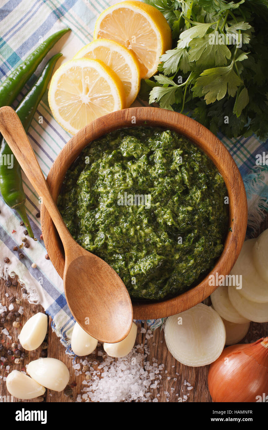 Chimichurri sauce with ingredients close-up on the table. vertical view from above Stock Photo