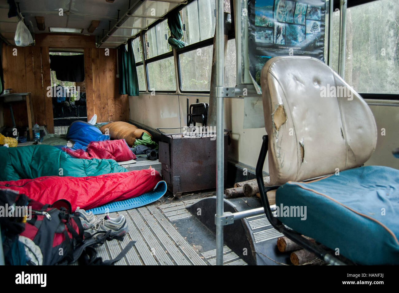 A group of travelers sleep inside an old bus transformed into a hostel - Stock Image