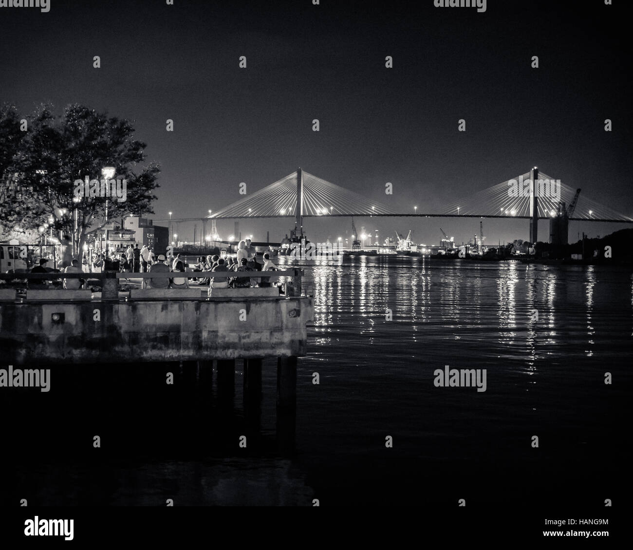 People gather by the quayside at night with a view of the Talmadge Memorial Bridge in Savannah - Stock Image