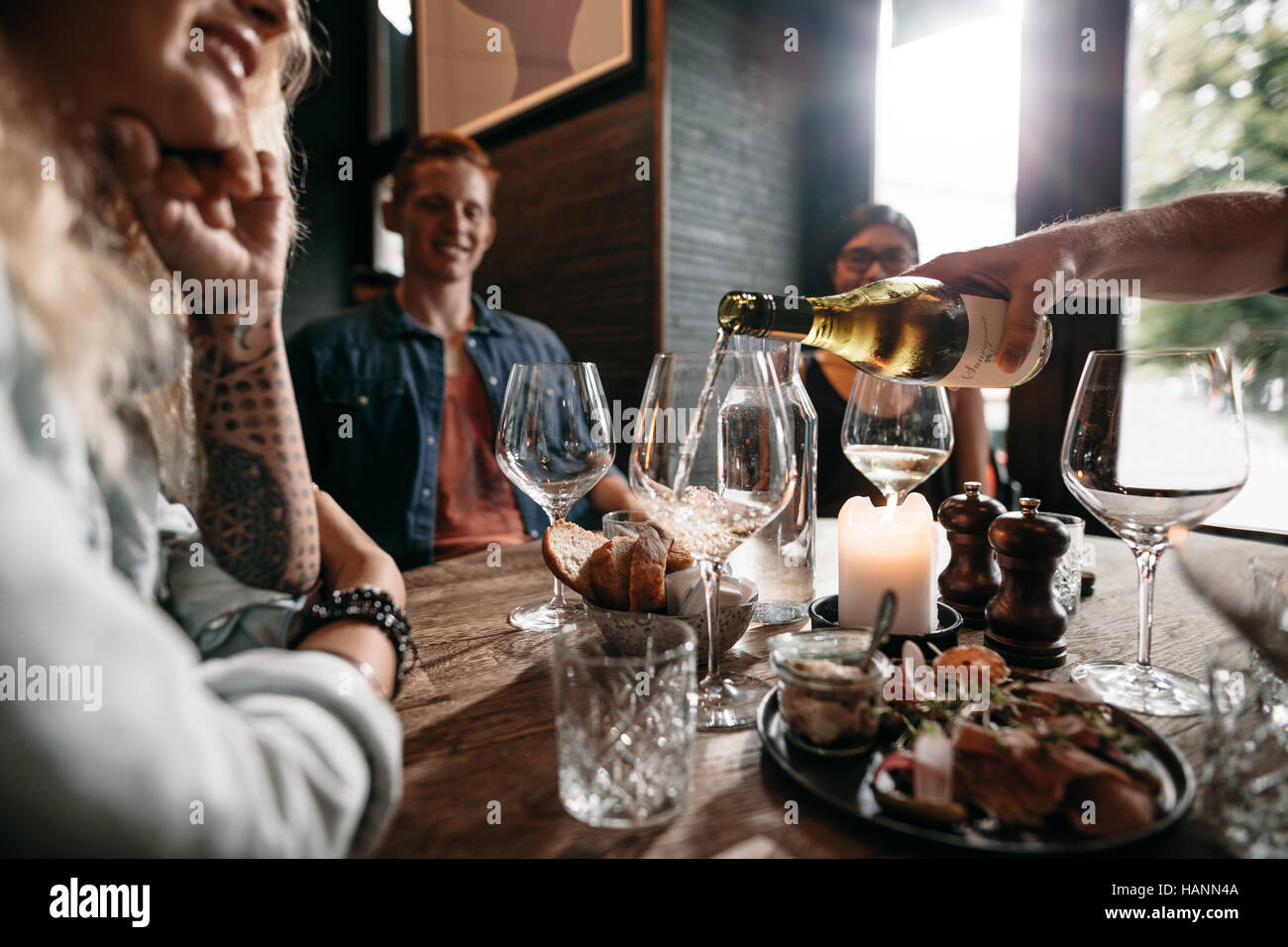 Man hand pouring white wine from the bottle into glasses with friends sitting around the table. Group of young people - Stock Image