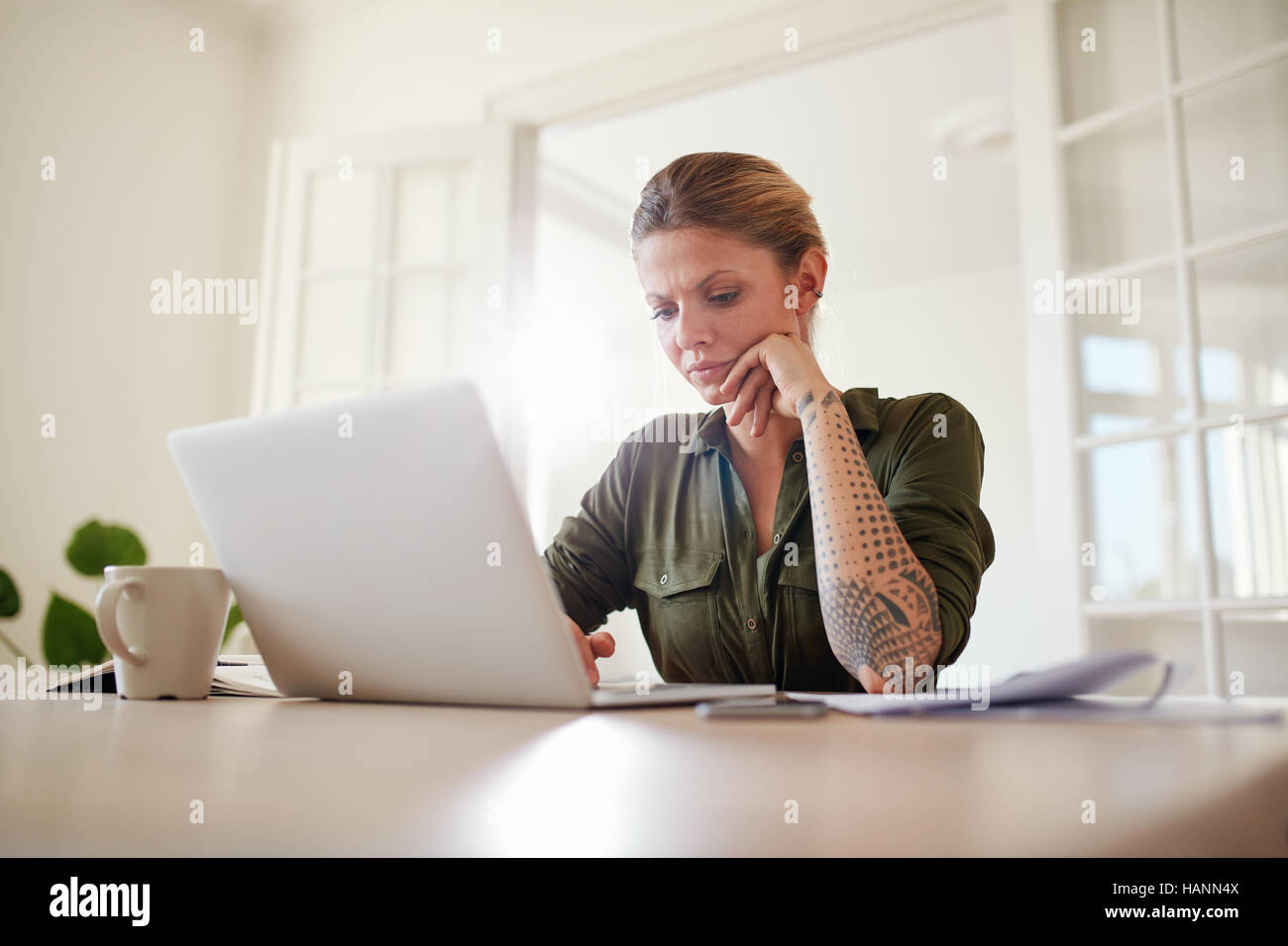 Indoor shot of beautiful female sitting at table and using laptop computer. Woman working seriously on laptop at Stock Photo