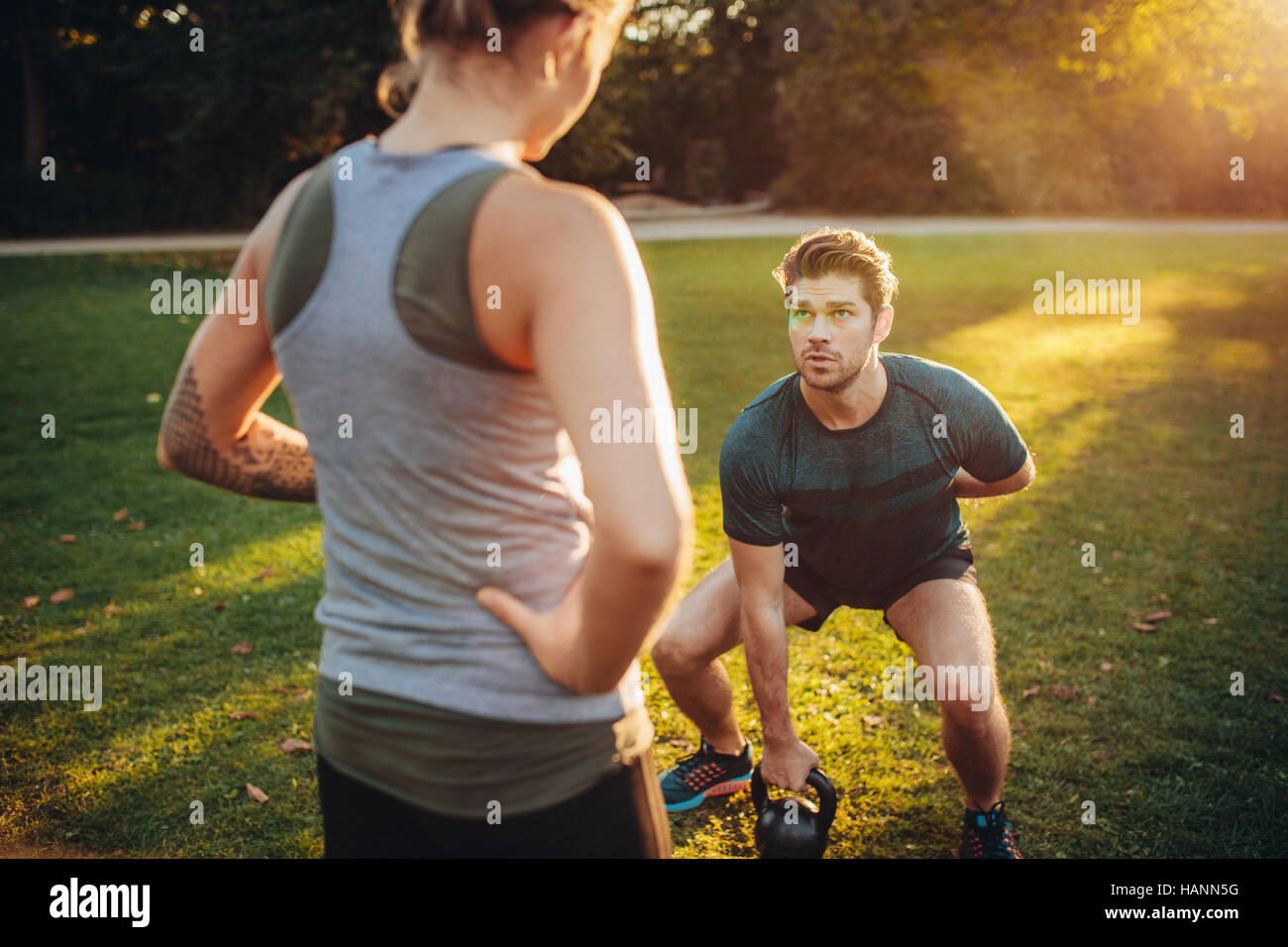 Female trainer guiding man while exercising with kettlebell in park. Personal trainer with man doing weight training - Stock Image