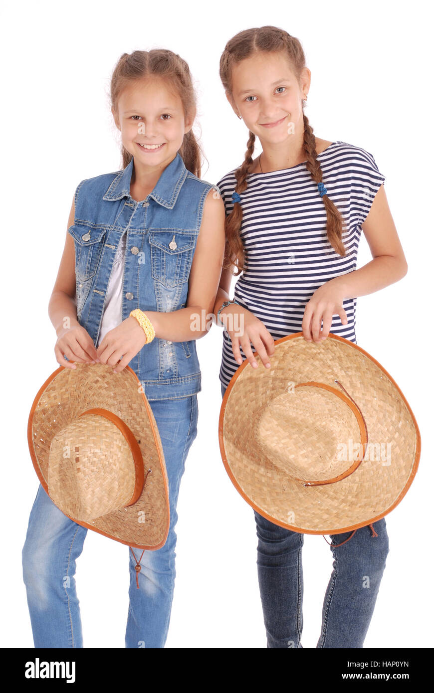 0f793c945af Two pretty twelve year old girls wearing a big floppy straw sun hat isolated  on white