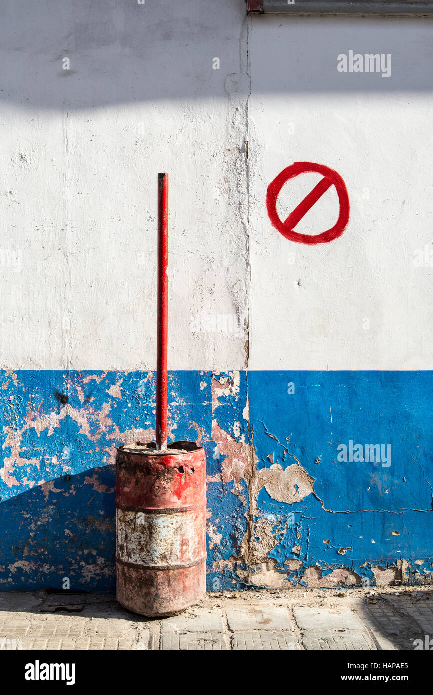 Old oil drum with red post concreted into it. There is a hand painted No Waiting sign painted on the wall. - Stock Image