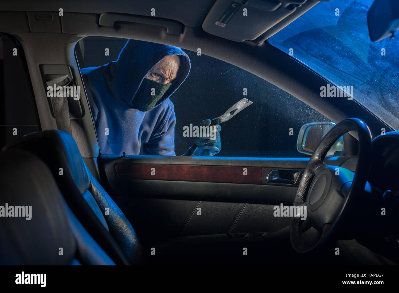 Car thief looking to break into a locked vehicle at night - Stock Image