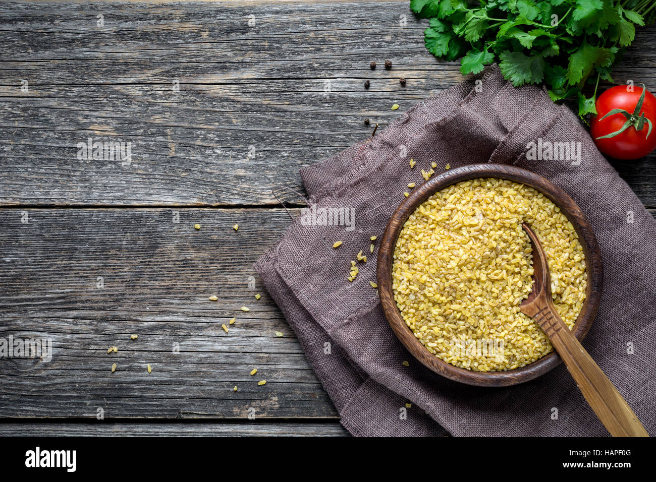 Bulgur (dry wheat grains) in wooden bowl, fresh parsley, tomato and spices on wooden table background. Top view - Stock Image