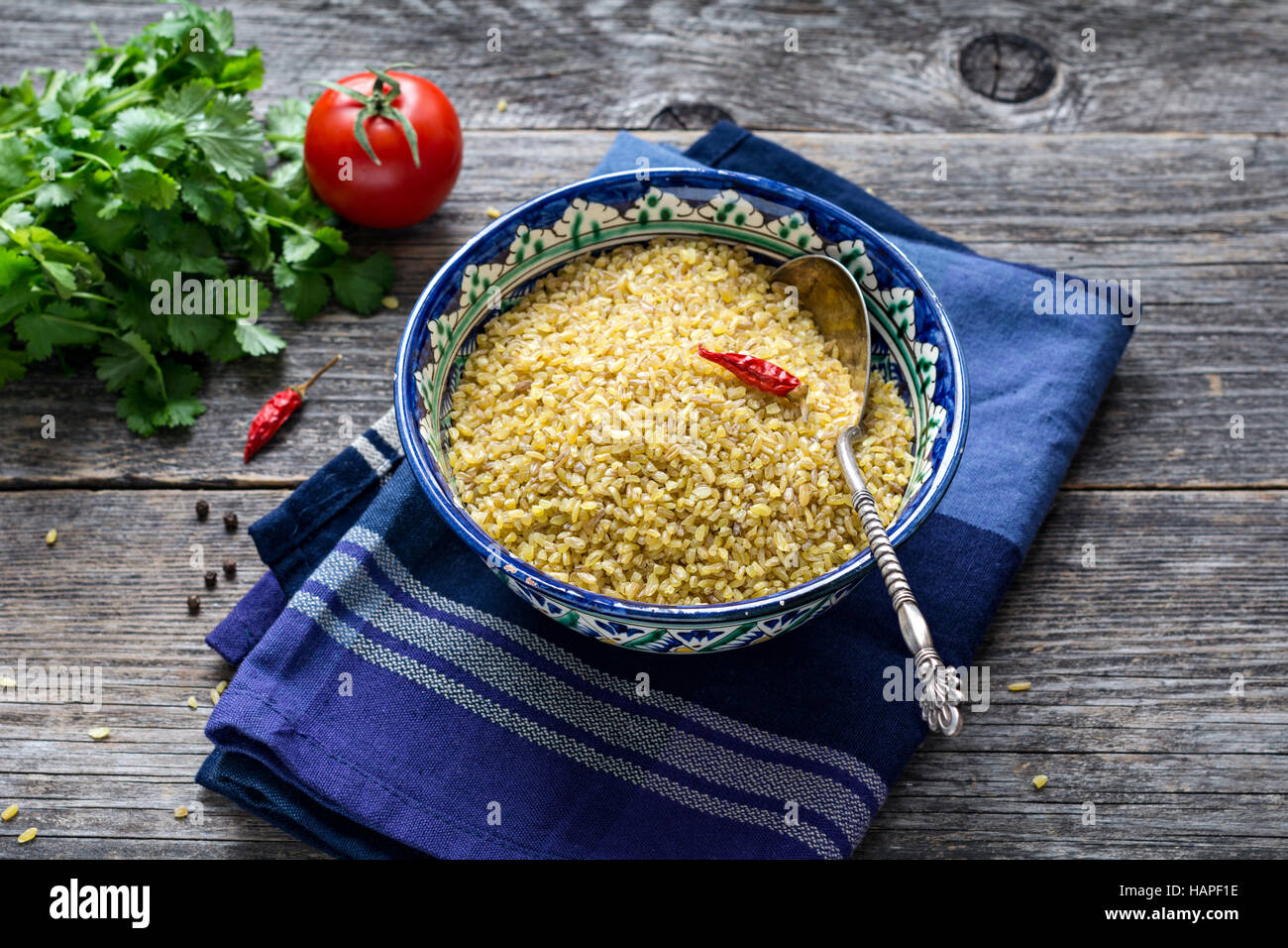 Raw bulgur wheat grains in colorful arabic bowl, fresh parsley, tomato and peppers for cooking. Wooden table background - Stock Image