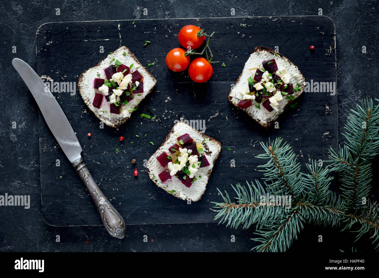 Vegan sandwiches with roasted beet and goat cheese on wooden cutting board, top view - Stock Image