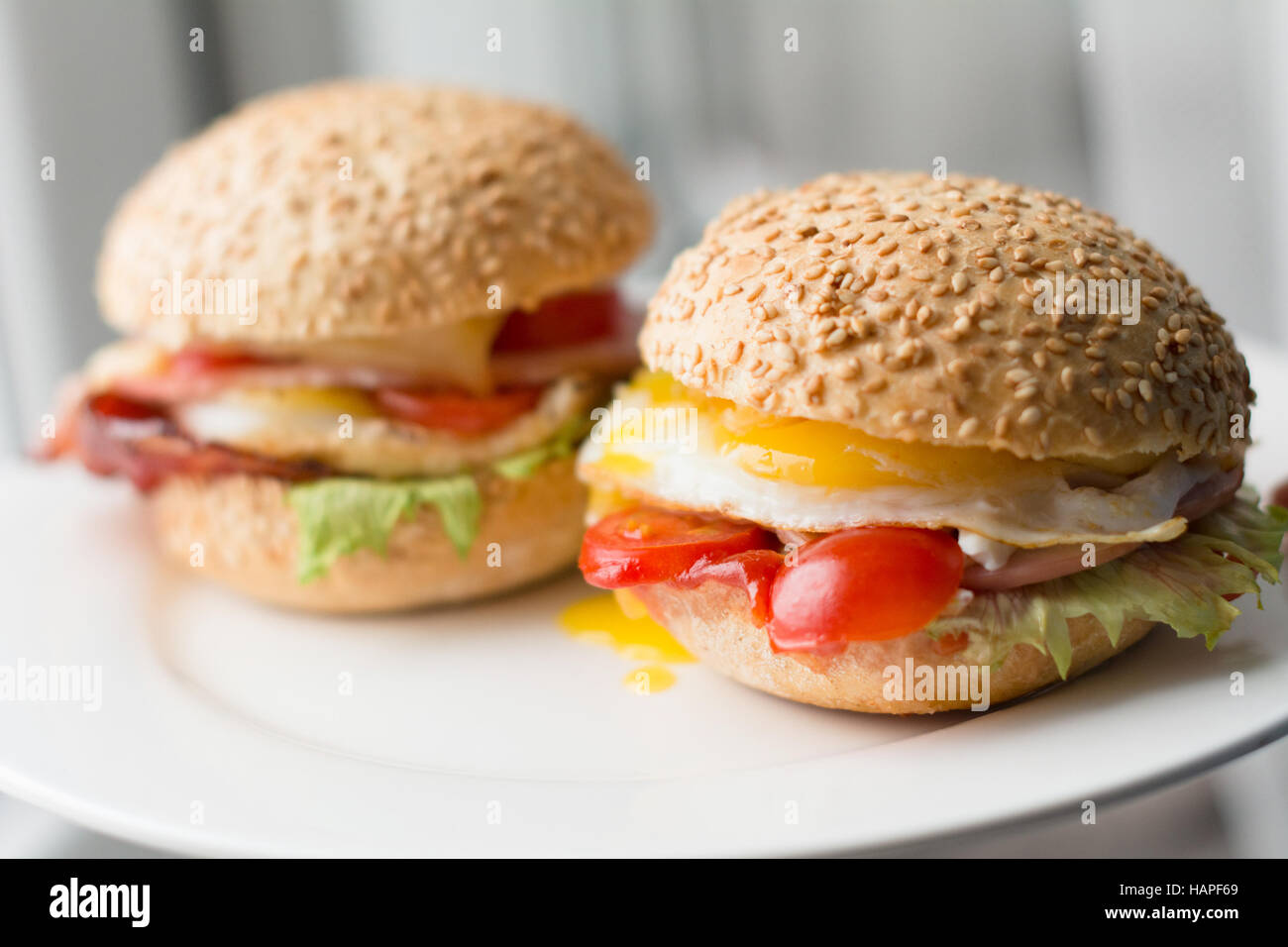 Bacon, egg and tomato sandwiches on white plate, close up view - Stock Image