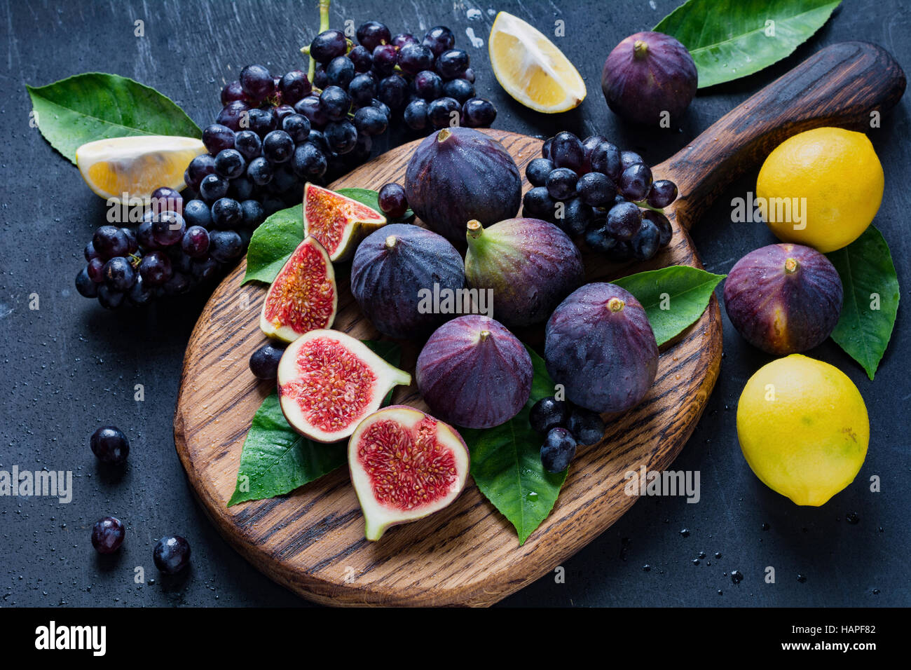 Fresh figs, black grapes and lemons. Fresh fruit variety on wooden cutting board - Stock Image