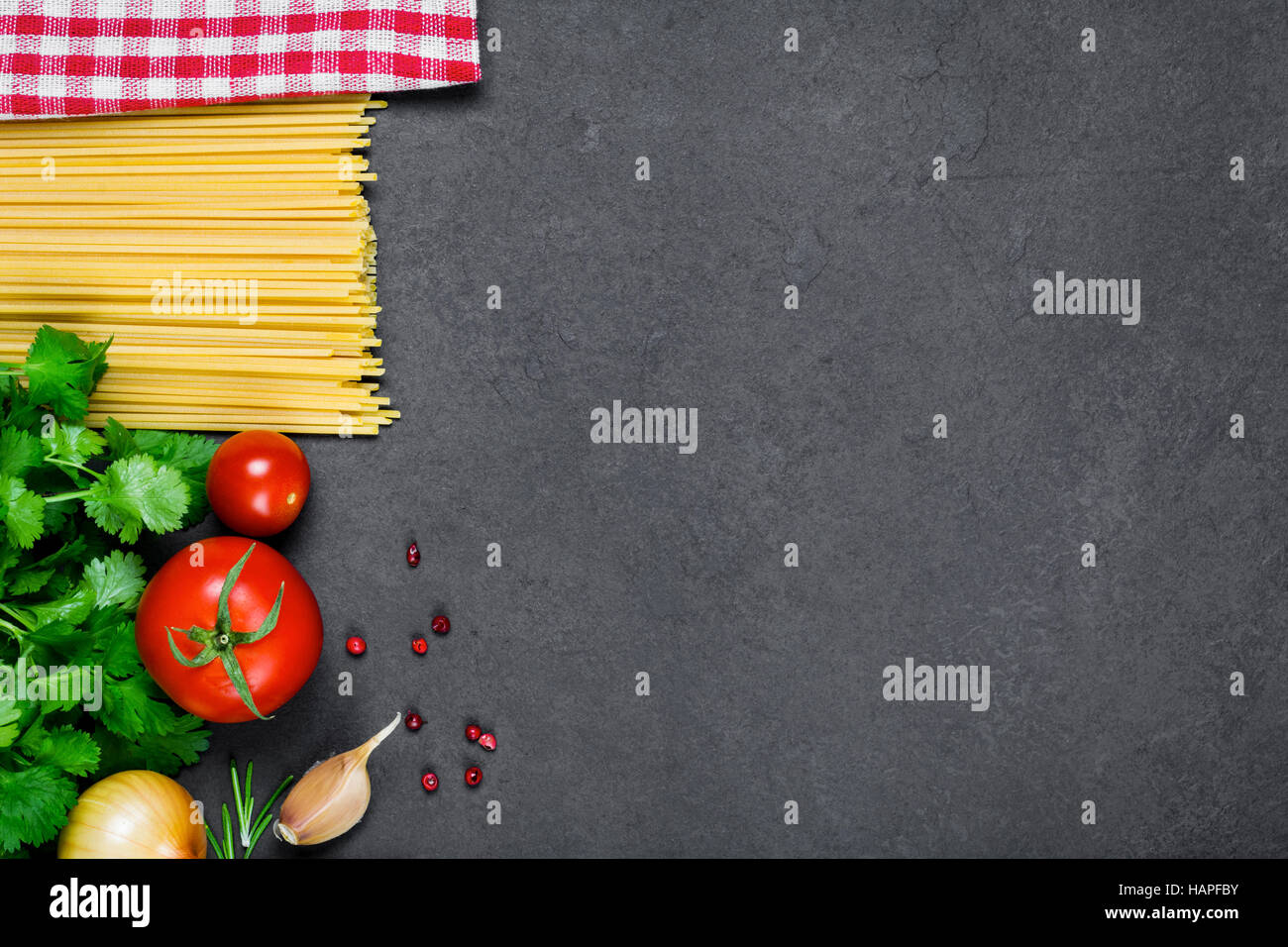 Cooking ingredients for italian cuisine: pasta spaghetti, tomatoes, parsley, onion, garlic, peppercorns and red - Stock Image