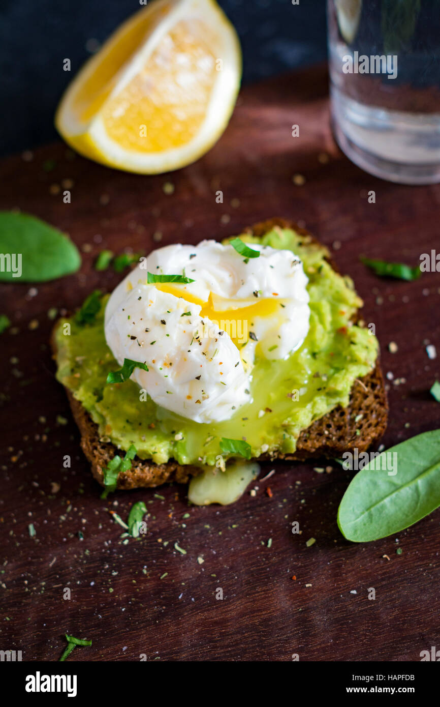 Mashed avocado and poached egg on toasted rye bread. Healthy breakfast, healthy snack - Stock Image