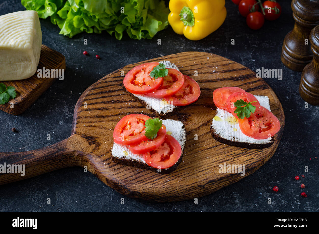 Healthy sandwich with fresh ricotta cheese, tomatoes and parsley on whole grain rye bread. Side view, front focus - Stock Image