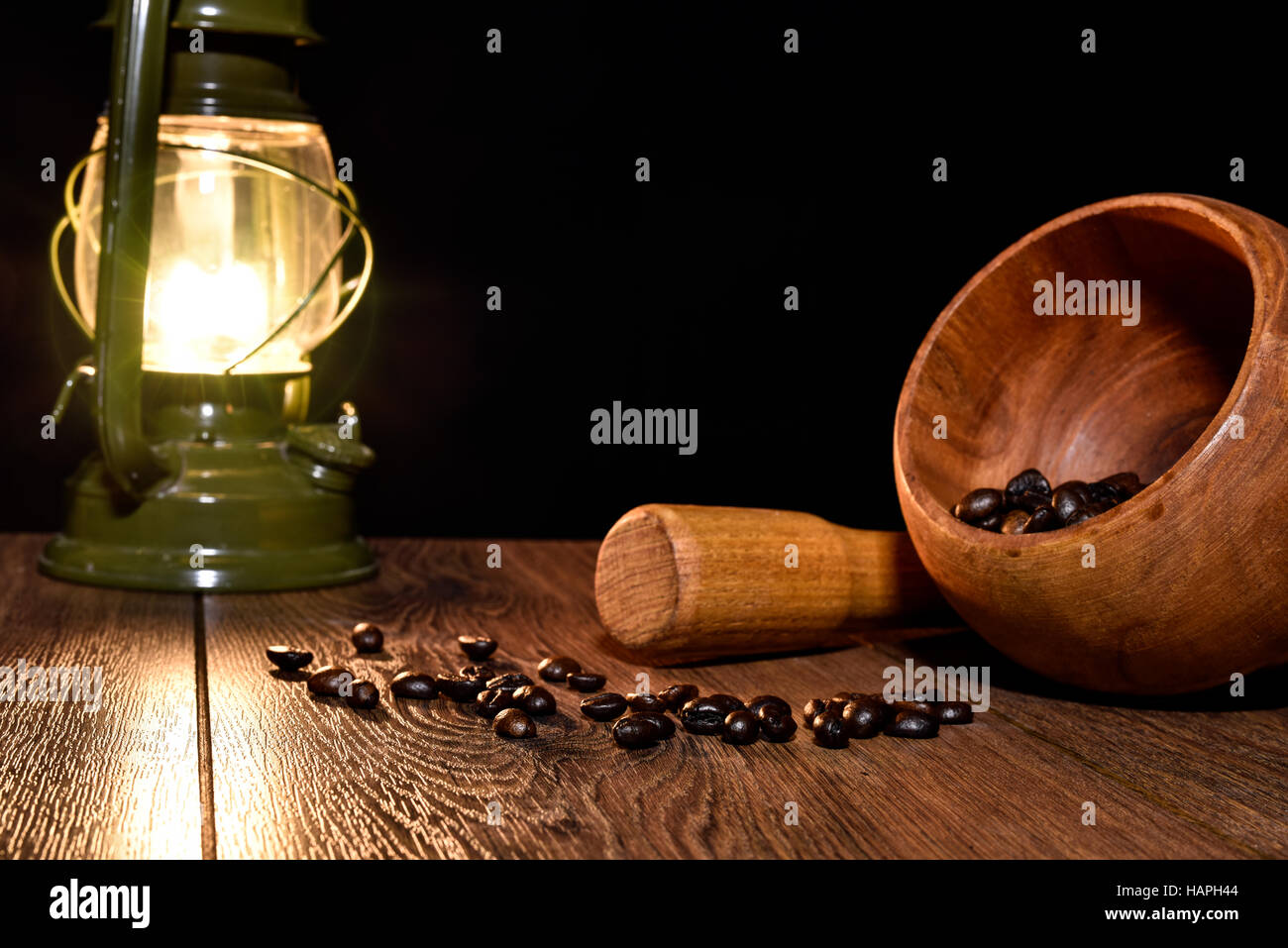 Grains of roasted coffee, kerosene lamp and mortar on the table - Stock Image