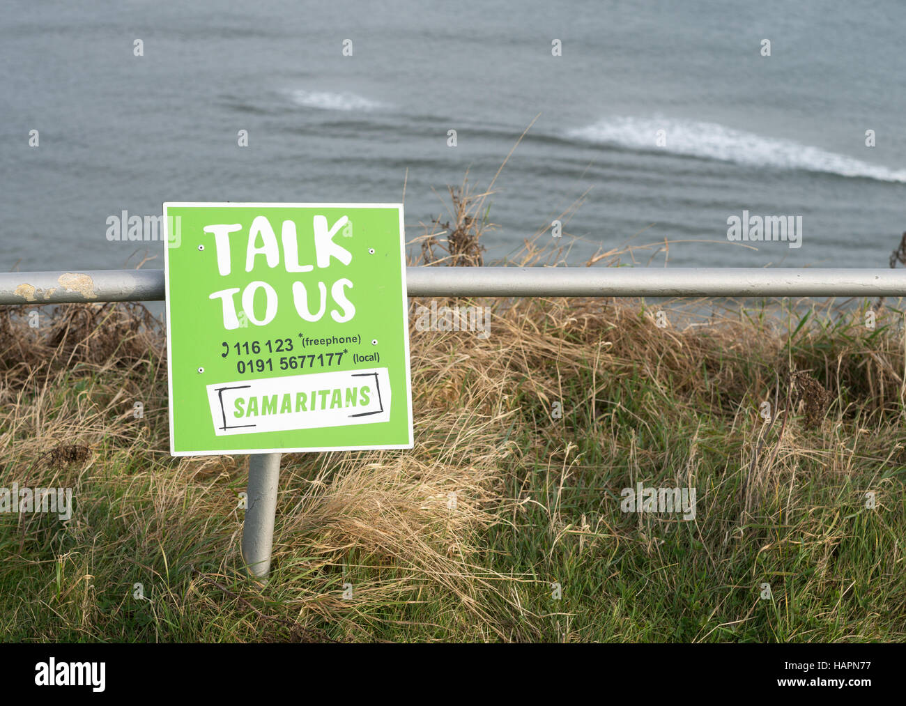 Samaritans sign above sea cliffs Talk To Us, The Leas, South Shields, South Tyneside, England, UK Stock Photo