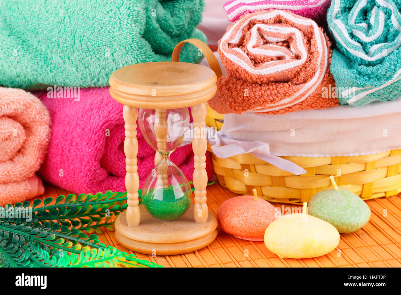 Spa set with colorful towels, candles and sand glass on bamboo background. Stock Photo