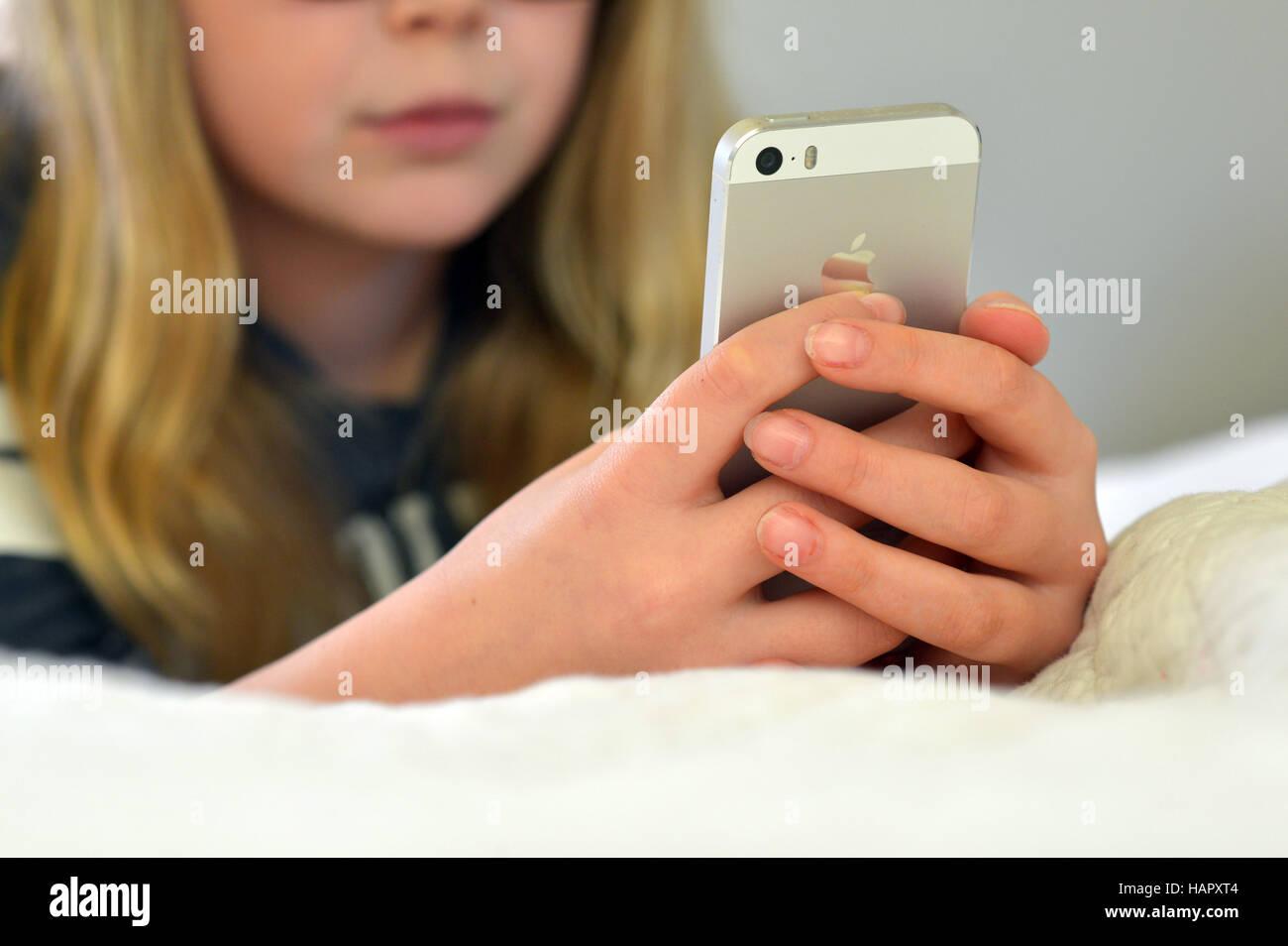 Teen / tween girl holding a mobile phone (iphone) - Stock Image