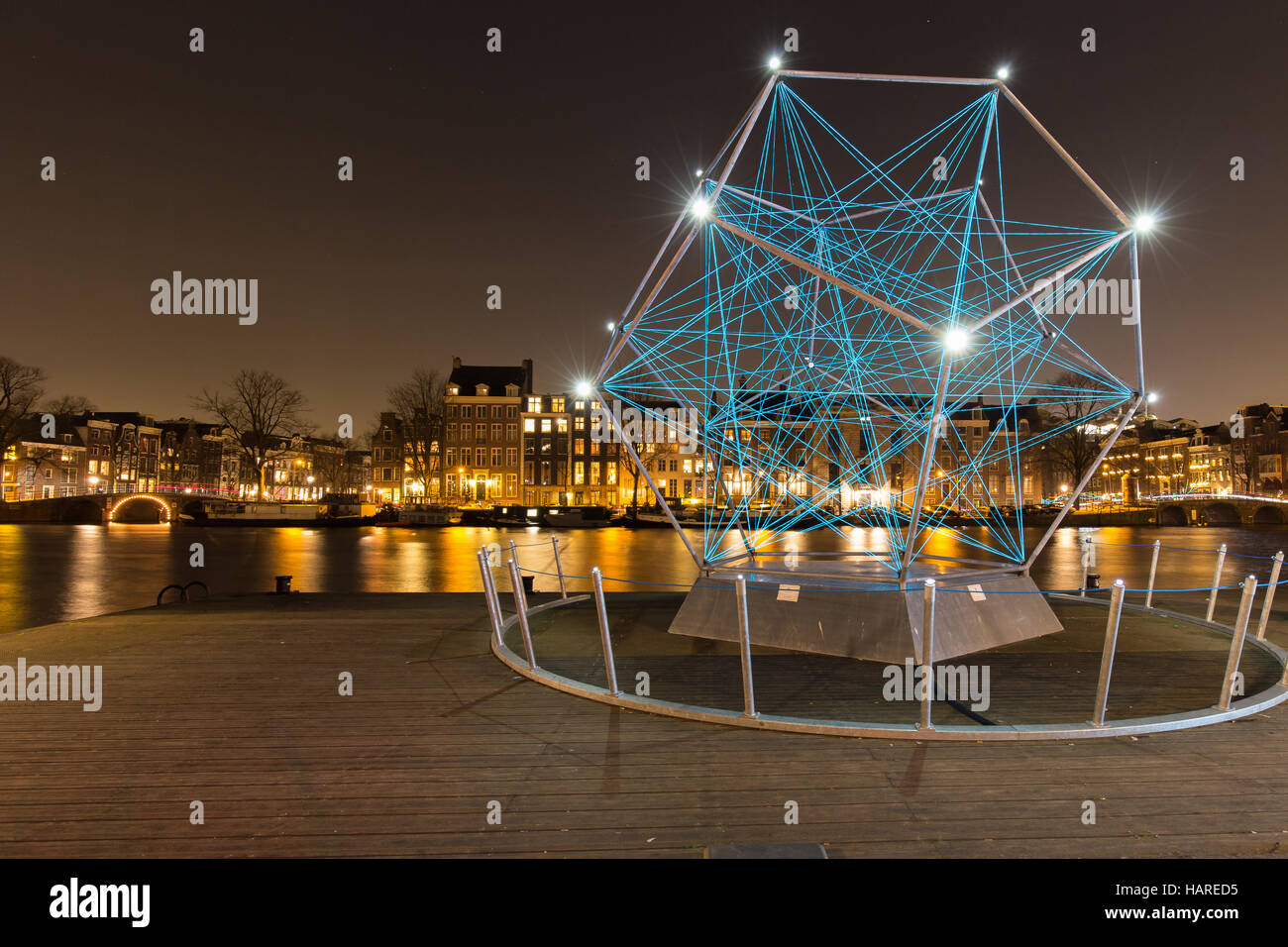 The Uniting Lightstar, an artwork by Venividimultiplex, decorates the Amstel river bank during the Amsterdam Light - Stock Image