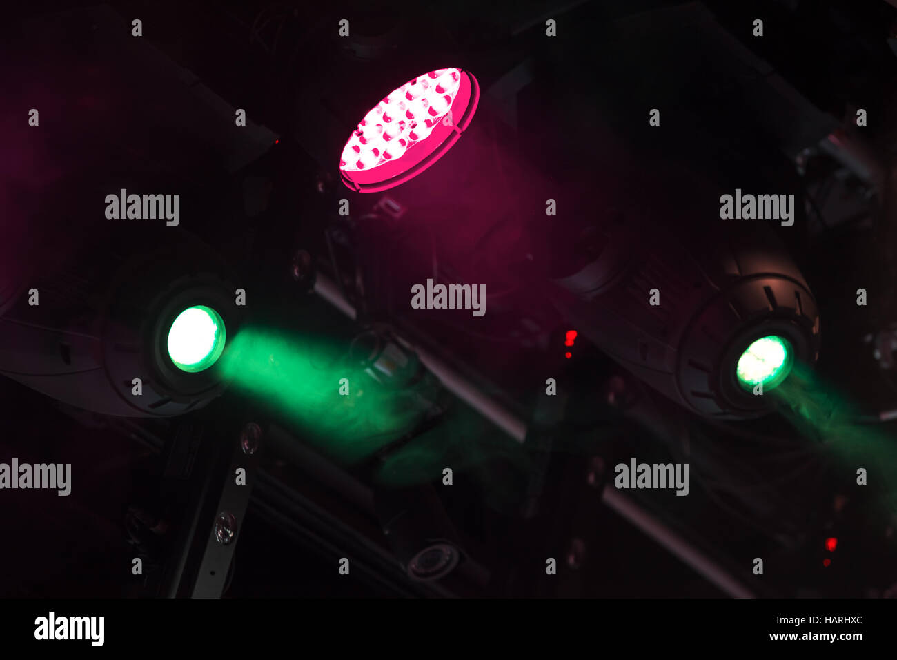 Colorful spot lights mounted above the stage - Stock Image